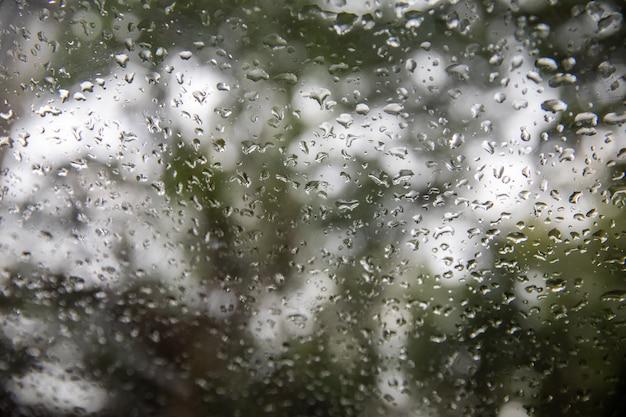 雨が降った後の車のフロントガラスの雨滴、雨季のガラス窓の水滴