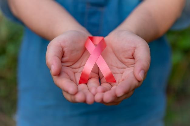 ヘルスケアと医療の概念 - 赤いリボンを持つ女性の手