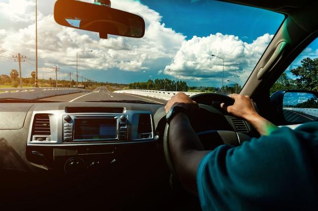 車の内装の道路で運転している男性
