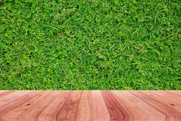 緑の草の抽象的なぼやけた背景の前に木製の机のイメージ。