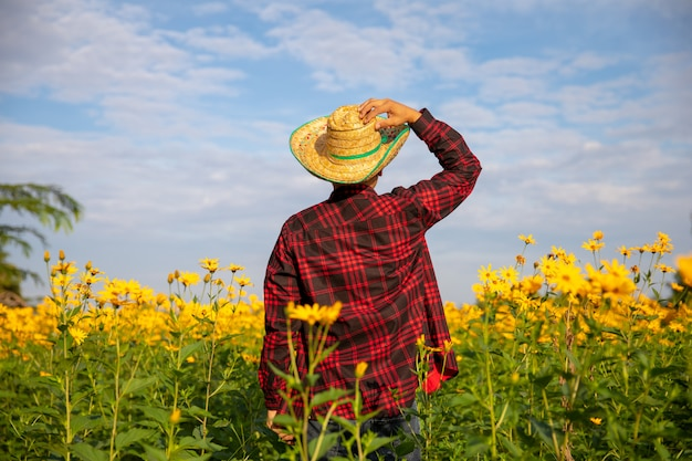 Вид сзади аграрного работника нося красную рубашку в желтом цветочном саде.