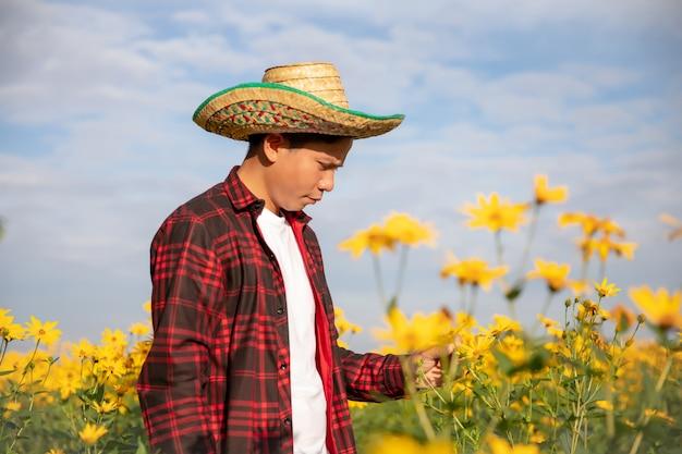 Колхозники осматривают солнечные летние цветы колхоза.
