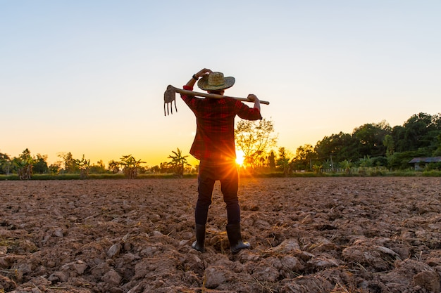 Фермер работает на поле на закате открытый