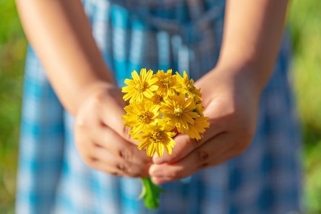 手は黄色の野生の花に愛を与える。ロマンチックな気持ち
