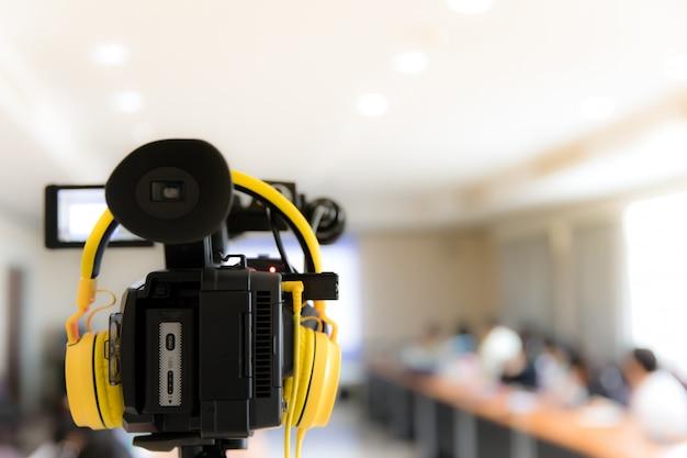 参加者とヘッドフォンを記録するビジネス会議室のビデオカメラ