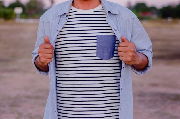 ビジネスマンは、白黒の縞模様のシャツを飾るためにシャツを開けています。