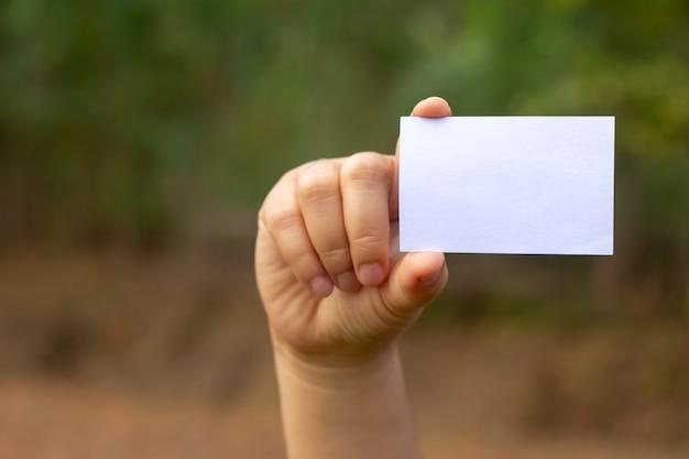 自然の背景に手に空白の名刺。モックアップ