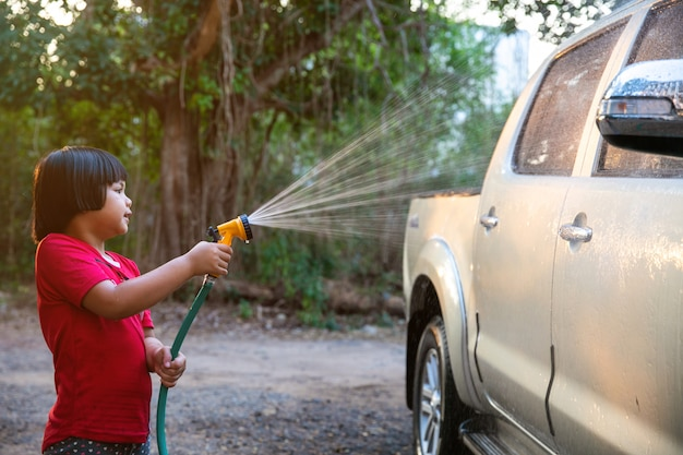 アジアの子供の幸せな女の子を助ける日光がかかる水の上の親洗車
