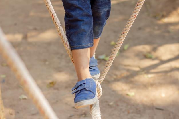 ロープの下を歩く子供たち