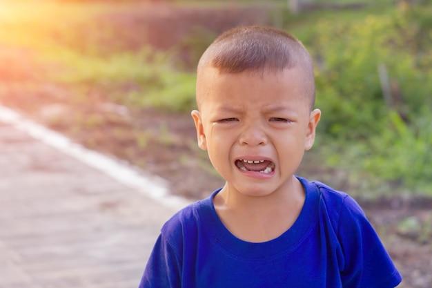 アジアの少年が路上で泣いています。