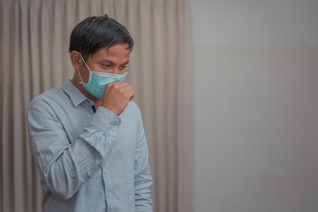 Мужской бизнесмен, который закрывает защитную маску из-за болезни и кашля