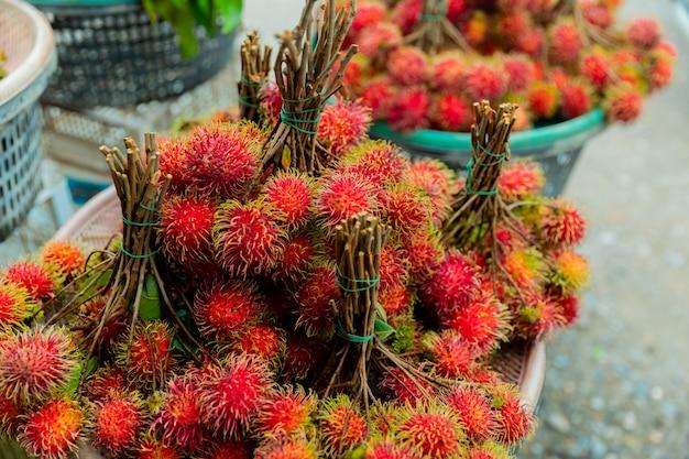 Предпосылка рамбутанов свежих фруктов, красные рамбутаны и желтые рамбутаны на местном рынке,