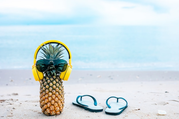 ターコイズブルーの海水に砂の上にスタイリッシュなミラーサングラスと金のヘッドフォンで熟した魅力的なパイナップル。熱帯の夏の休暇の概念。