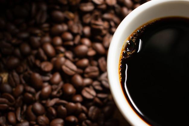 ぼやけローストコーヒー豆と白いセラミックコーヒーカップのブラックコーヒー