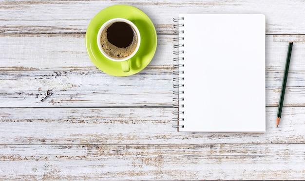 空のノートパッドと鉛筆の木のコーヒーのカップ