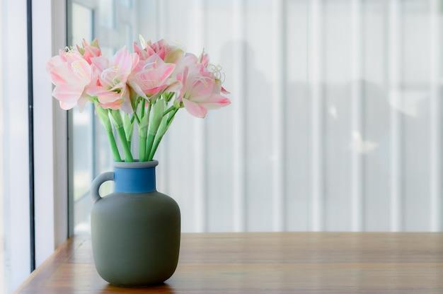 Красивая розовая искусственная лилия в серой вазе для керамики на фоне коричневого дерева.
