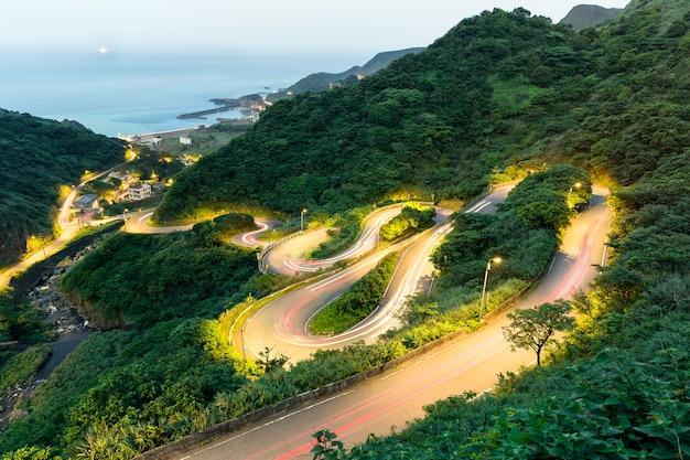 夕暮れの海の眺めを持つ芝生の丘の曲がる道