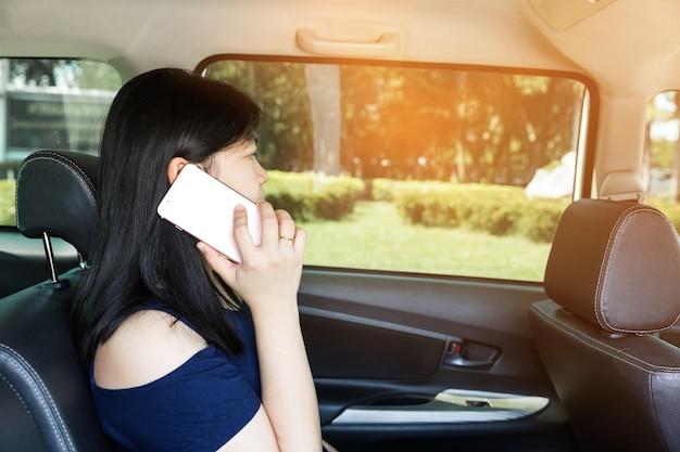 車で携帯電話を持つ美しい女性