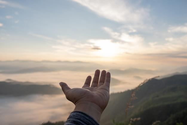 手を広げて自然光と山の景色を眺める