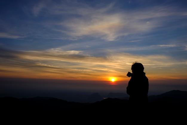シルエットスタイル美しい少女魅力的なスタンドコーヒーと自然の美しさを眺めを楽しみます。朝の日の出時にはゴールドマウンテンビューとハイアングルからの美しい眺め。