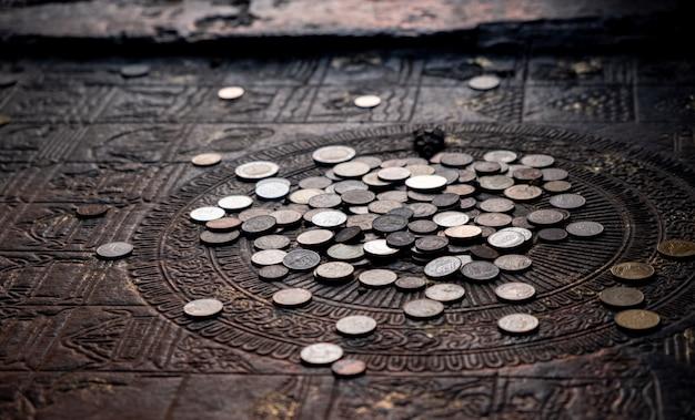 Тайская монета, оставленная на полу храма. таиланд считает, что бросание монеты оставлено на благотворительность.