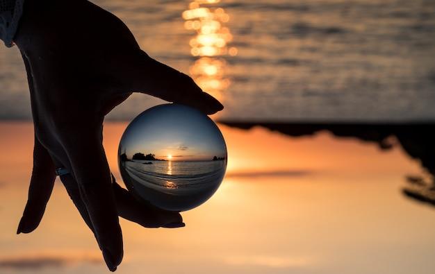 クリスタルボール夜の日没のビーチを反映