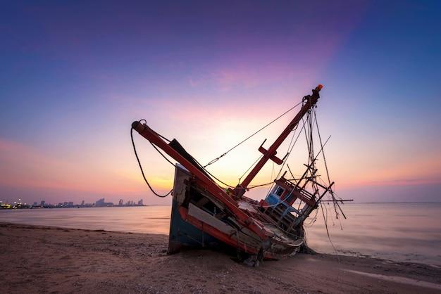 トワイライト時間にビーチで木製漁船の放棄された難破船