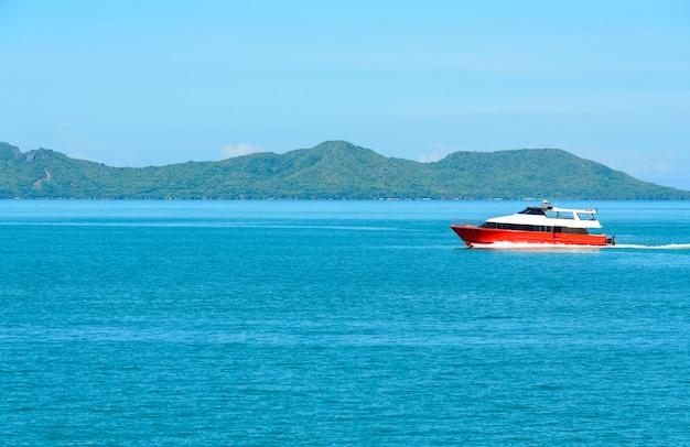 朝の青空の下で赤いボートと海がある風景