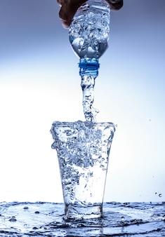 Выливание воды и брызг в стекле с отражением на зеркале