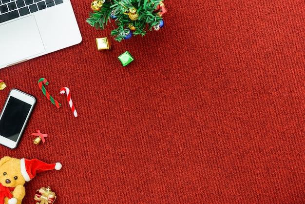 トップビューコンピューターとクリスマス祭りのテーマの背景を持つビジネスコンセプトの電話。
