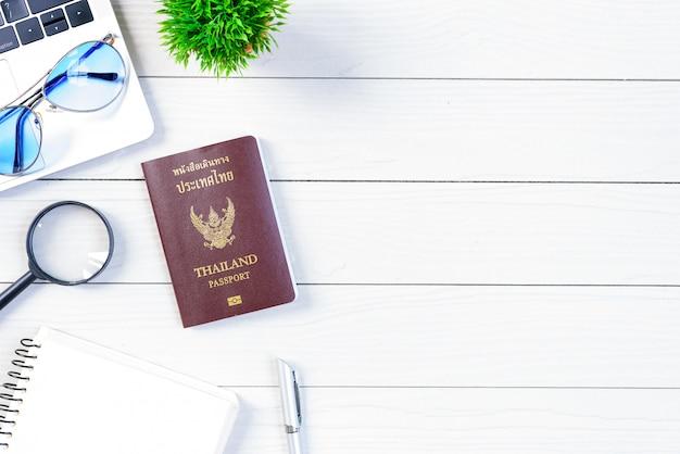 У рабочего и служащего тайских людей есть поездка, мечтающая и готовящаяся к путешествию и путешествию по миру с ноутбуком и таиландским паспортом на белом деревянном столе с плоской плоской поверхности.