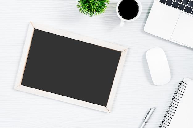 ホワイトウッドのオフィスデスクテーブルと上面図とフラットレイの概念でコーヒーと空白板を操作するための機器。