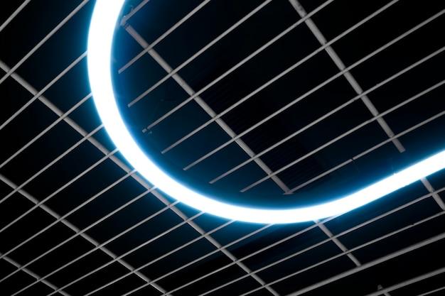 Освещенная кривая неоновая подсветка украшения висит внизу на потолочном гриле. конструкция потолка современного дизайна украшена гибкой неоновой светодиодной полосой
