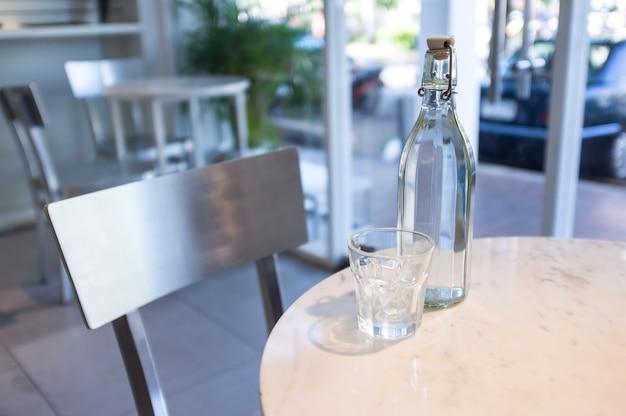 白い背景の白い大理石のテーブルに空のガラスのカップと白水のボトル
