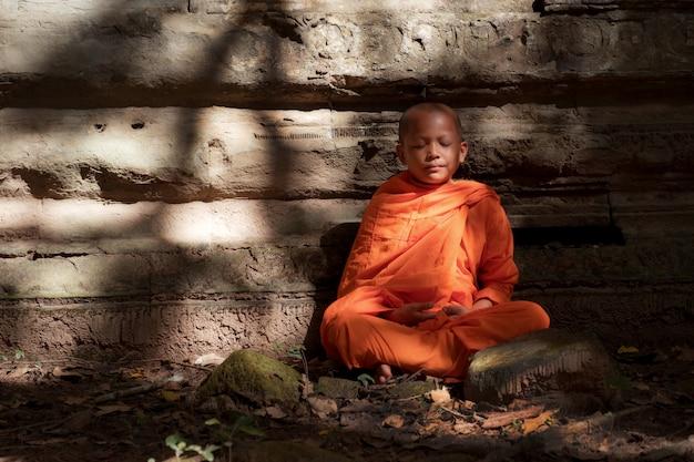 初心者は古代の場所で瞑想しています。