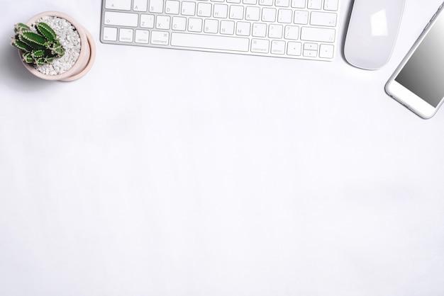 その上にたくさんのものを持つ白い事務机のテーブル。コピースペース平面図
