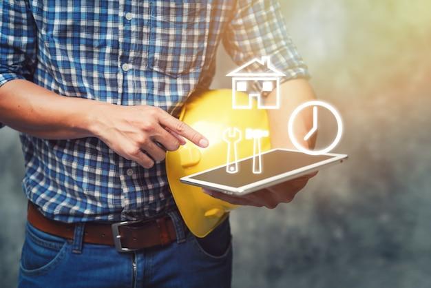 エンジニアのヘルメットを押しながらタブレット建設プロジェクトのチェックを使用してください。