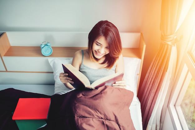 アジアの女性が自宅の寝室で本を読んで朝の日差し。