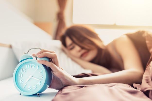クローズアップ若い眠っている女性と自宅の寝室で目覚まし時計をオフにする手を上げる