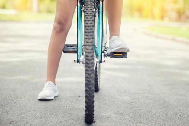 若い女性は公園で夕日にサイクリングします。