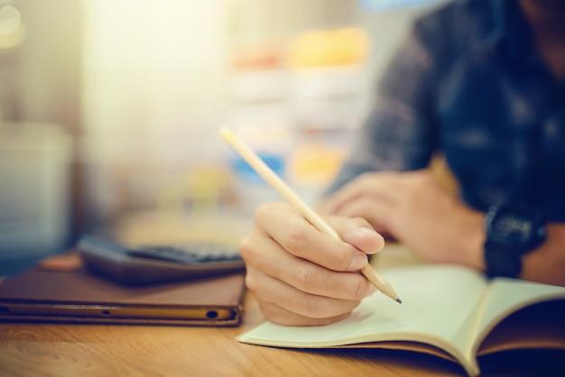 ノートに書くペンで実業家の手のクローズアップ。ビジネスと教育の概念