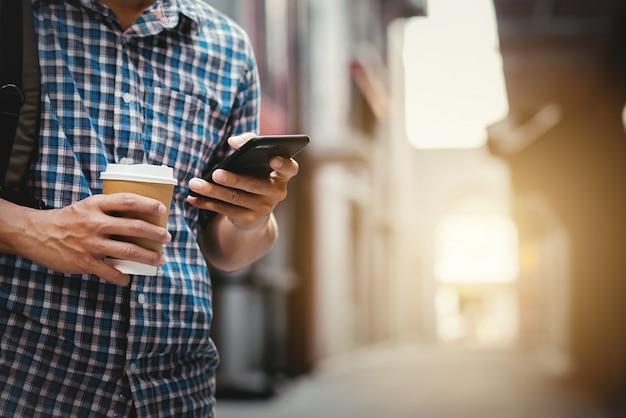彼の携帯電話と路上でコーヒーのカップを使用している人のクローズアップ。ショッピングや旅行のコンセプトです。
