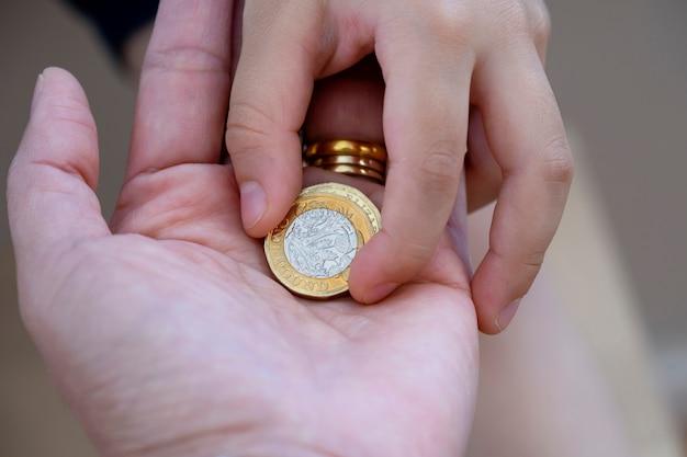 Рука малыша дает две фунт монеты на руке женщины