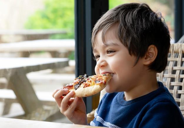 トリミングショットかわいい子供男の子の家で食べるピザをカフェで