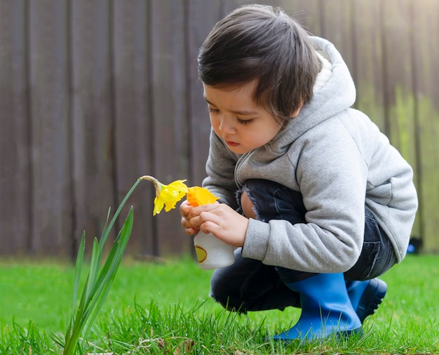 庭で花に水をまくスプレーボトルを使用して子供