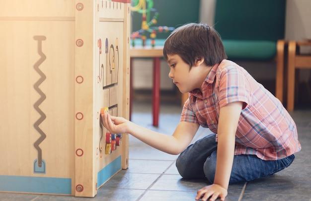 Крытый портрет дошкольника мальчик играет в детском клубе с марочных тон