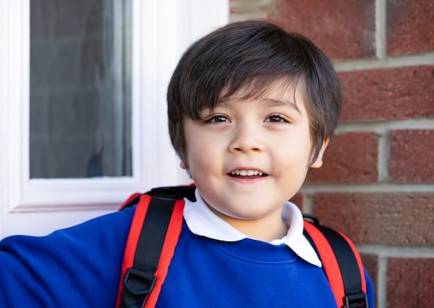 Портрет рюкзака нося счастливого мальчика готовится пойти в школу в утре.