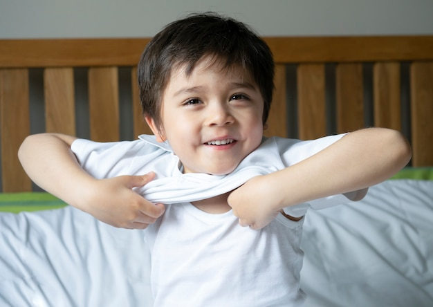 Школьник сидит в постели и пытается носить свою одежду с улыбающимся лицом, милый мальчик-мальчик одевается и готовится к школе, униформа для ребенка в спальне, готовой к школе, снова в школу