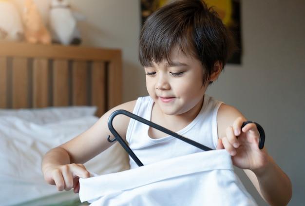 笑顔でかわいい子供は、朝学校に行く準備をします。