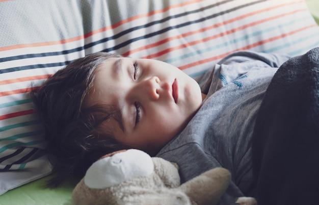 ベッドで寝ている愛らしい子供、彼のベッドで眠っているかわいい男の子、美しい眠そうな男の子